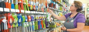 "LOUSIA EDGERTON, an employee at Now You're Cooking, arranges some kitchen tools on the ""gadget wall"" at the Bath store."