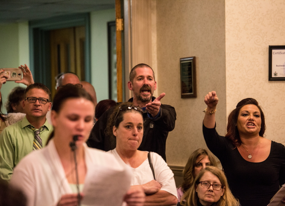 Greg Blouin, left, and Mellisa Luedke, right, object to Biddeford city councilors after Mayor Alan Casavant banged his gavel to close the public comment portion of Tuesday night's emotional council meeting.  Whitney Hayward/Staff Photographer