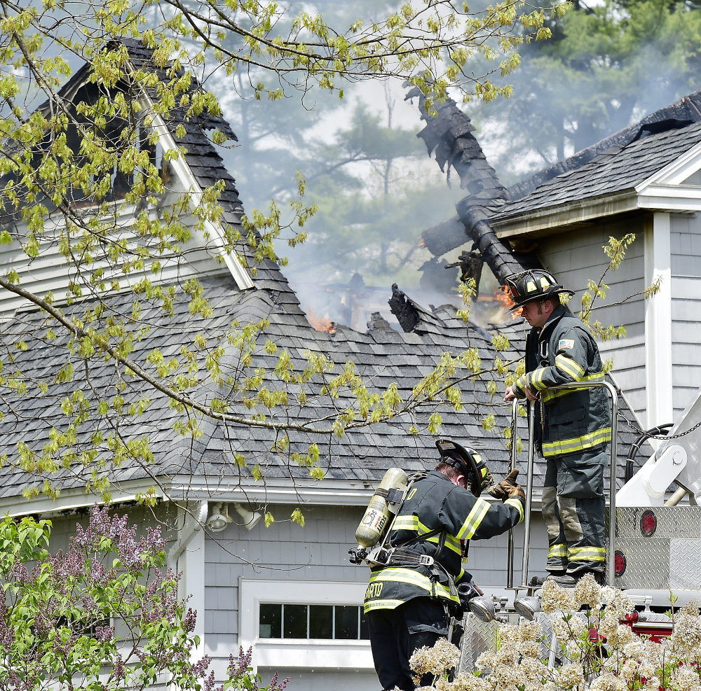 Firefighters climb down from a ladder truck while fighting a house fire at 2 Beaver Brook Road in Scarborough on Friday.