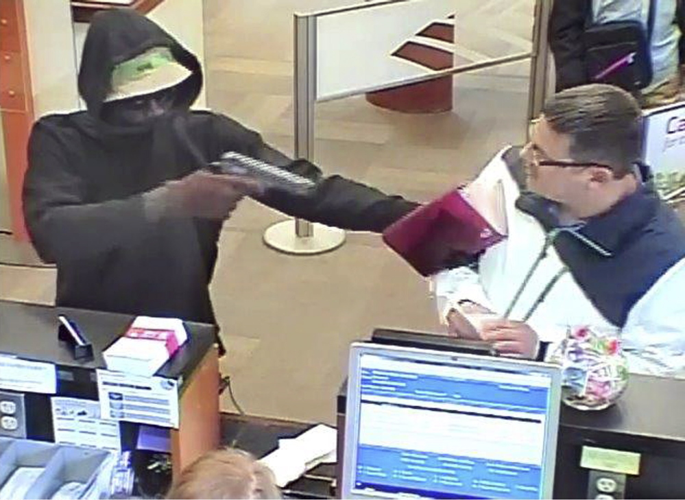 A robber points a gun at a man during the robbery of the Bank of America branch at One City Center in Portland on June 19, in this image from a bank security camera.