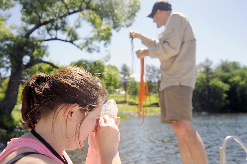 Amy Havens scrutinizes algae that Robin Sleith, right, collected Wednesday from the bottom of Minnehonk Lake in Mount Vernon.