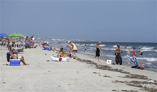 Vacationers relax on the beach and in the surf in Oak Island, N.C., Monday following Sunday's shark attacks that severely injured two people within an hour and about  2 miles from each other. The Associated Press