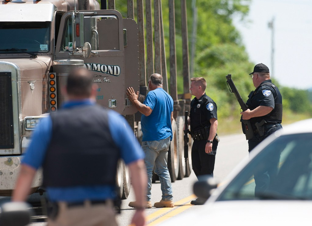 Lincoln police Chief Daniel Summers, right, and Officer Josh McKechnie inspect a logging truck leaving the town of Lee on Friday. Kevin Bennett Photo