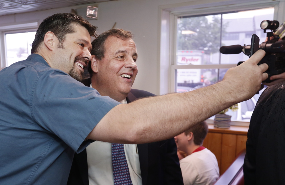 New Jersey Gov. Chris Christie poses for a selfie with a Becky's Diner patron. Christie said Wednesday the endorsement by Gov. Paul LePage is the first by a sitting Republican governor for any of the party's White House hopefuls.