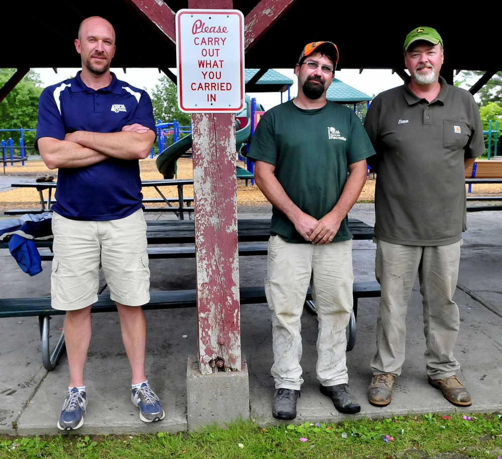Matt Skehan, left, director of Waterville Parks and Recreation, and employees Sam Green and Steve Buzzell stand beside a sign urging users to remove their trash at the North Street playground and other city parks in Waterville.