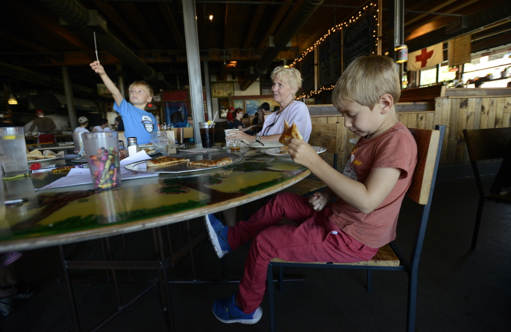 Patricia Finkelstein of Scarborough dines at Flatbread Co. in Portland with her family, including Gavriel Steinherr, 3, left, and Akivah Steinherr, visitors from Switzerland. The boys' mother, Evelyn Steinherr, said restaurants in the states are more family-friendly than at home.