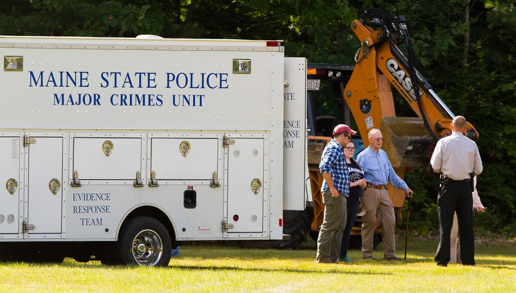 Investigators confer Sunday near the state police major crime unit truck at the search scene for Kimberly Moreau near Route 108 in Canton. A back hoe was among the equipment used to dig for evidence in case.