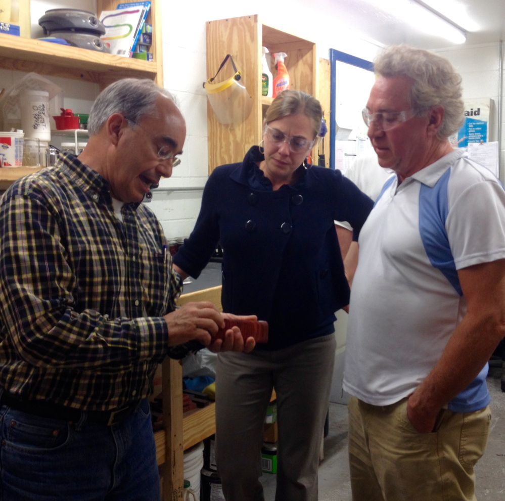 Rep. Bruce Poliquin looks at a product made by Cousineau Wood Products in North Anson with Samantha Warren, his district director. At right is Randy Cousineau, the company's CEO.