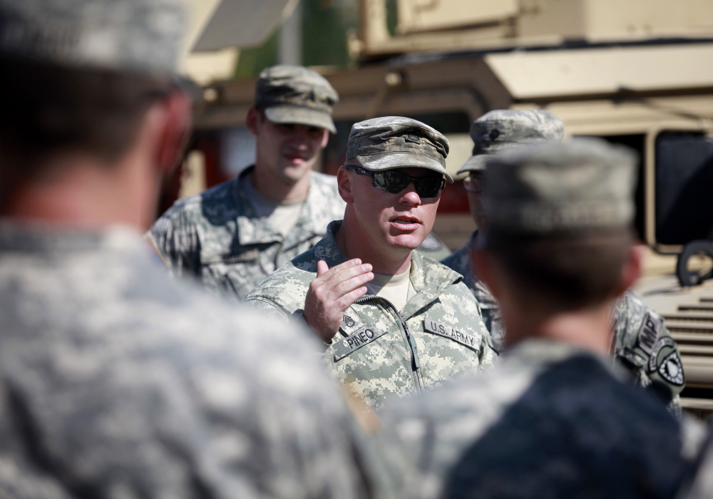 The Portland Police Department and the Maine Army National Guard's 488th Military Police Company work together Wednesday in a training exercise that tests the abilities of the two departments to work together in a stressful environment. Sgt. Dwight Pineo speaks to a group of soldiers at the training location. Derek Davis/Staff Photographer