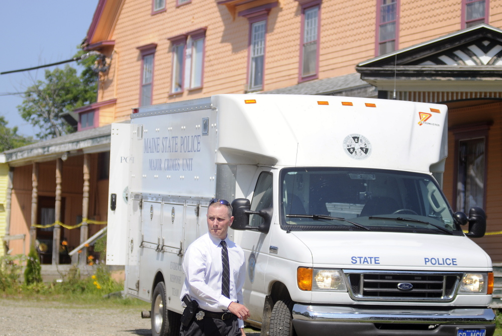 A Maine State Police detective walks out of the driveway of an East Pittston boarding home while investigating the fatal stabbing of the landlord in August.