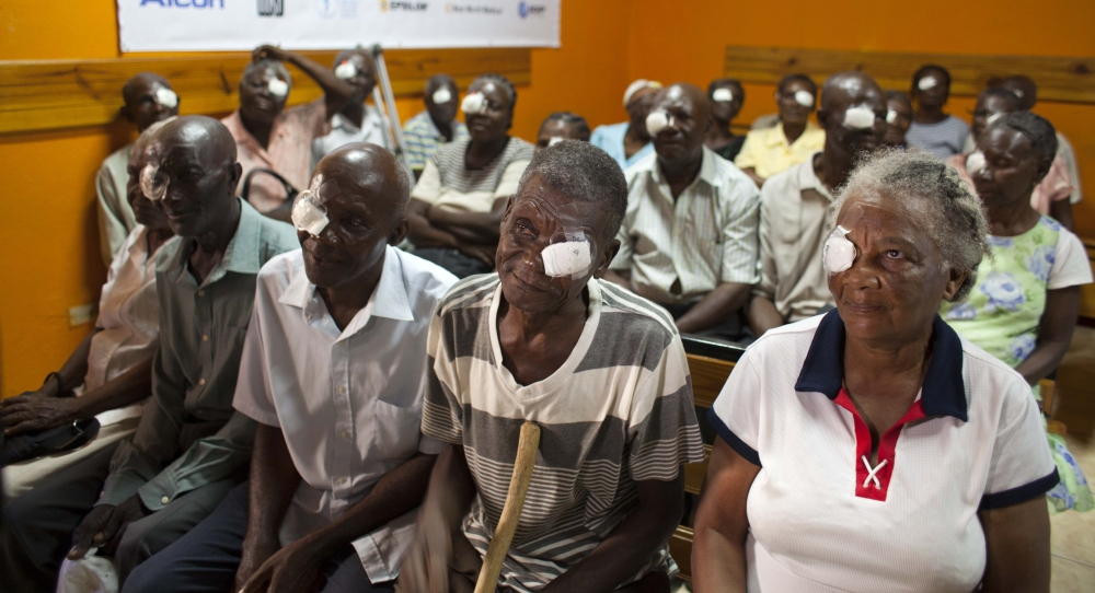 Mathieux Saint Fleur, 75, second from right, waits with other patients who had cataracts removed to have their bandages taken off one day after surgery in Cap-Haitien, Haiti.
