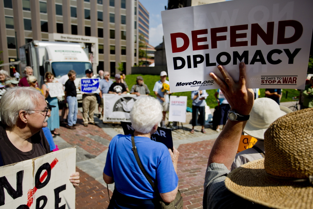 Gary Anderson of Bath holds up a sign as he and other activists gather in Portland's Monument Square on Wednesday to urge Sen. Susan Collins to back the Iran nuclear agreement. Collins has not yet disclosed her position.
