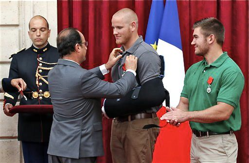 French President Francois Hollande pins the Legion of Honor medal on U.S. Airman Spencer Stone while Alek Skarlatos a U.S. National Guardsman applauds at the Elysee Palace, Monday in Paris. Stone, Skarlatos and their friend Anthony Sadler subdued a gunman as he moved through a train with an assault rifle strapped to his bare chest. A British businessman, Chris Norman, also jumped into the fray, and also received the medal on Monday. The Associated Press