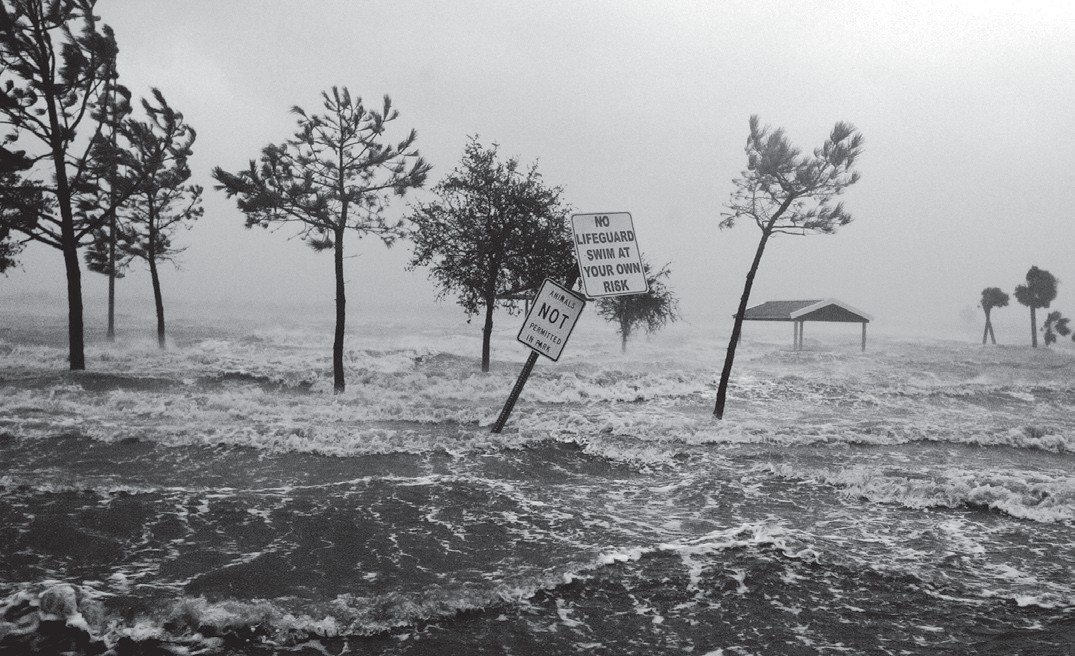 In this 2005 file photo, swirling floodwaters of Lake Charles lap onto the shore in the port city of Lake Charles, La., following landfall of Hurricane Rita.