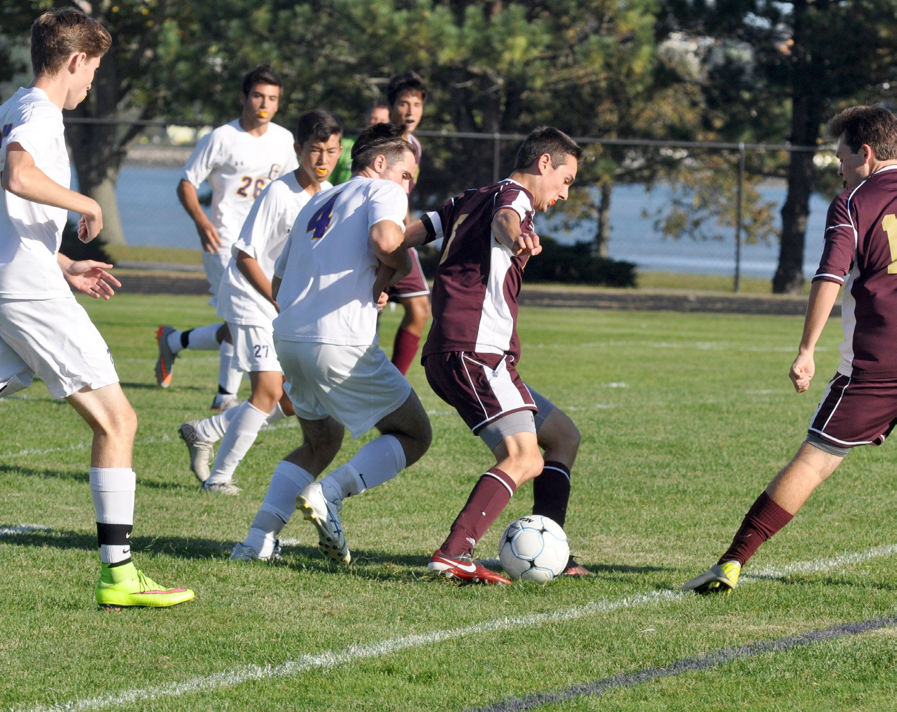 Thornton Academy's Alex Arnold, center right, shields the ball from Cheverus' Will Peterson (4) as Cheverus' Brady Levesque, far left, and Thornton's Anthony Palamountain, far right, look on during the Trojans' 2-1 victory at Boulos Stadium in Portland Thursday.