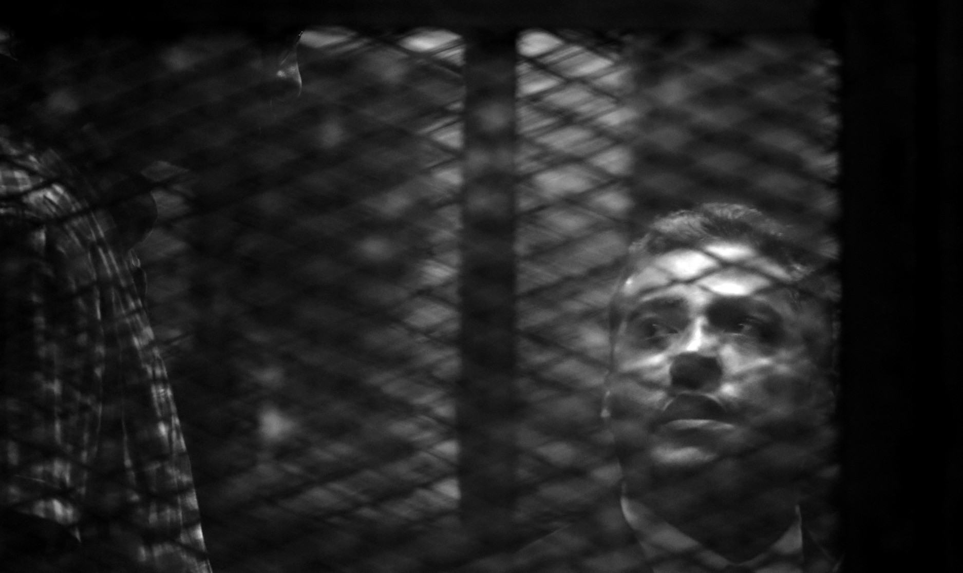 In this Aug. 29 file photo, Canadian Al Jazeera English journalist Mohammed Fahmy listens to his verdict in a soundproof glass cage inside a makeshift courtroom in Tora prison in Cairo, Egypt.