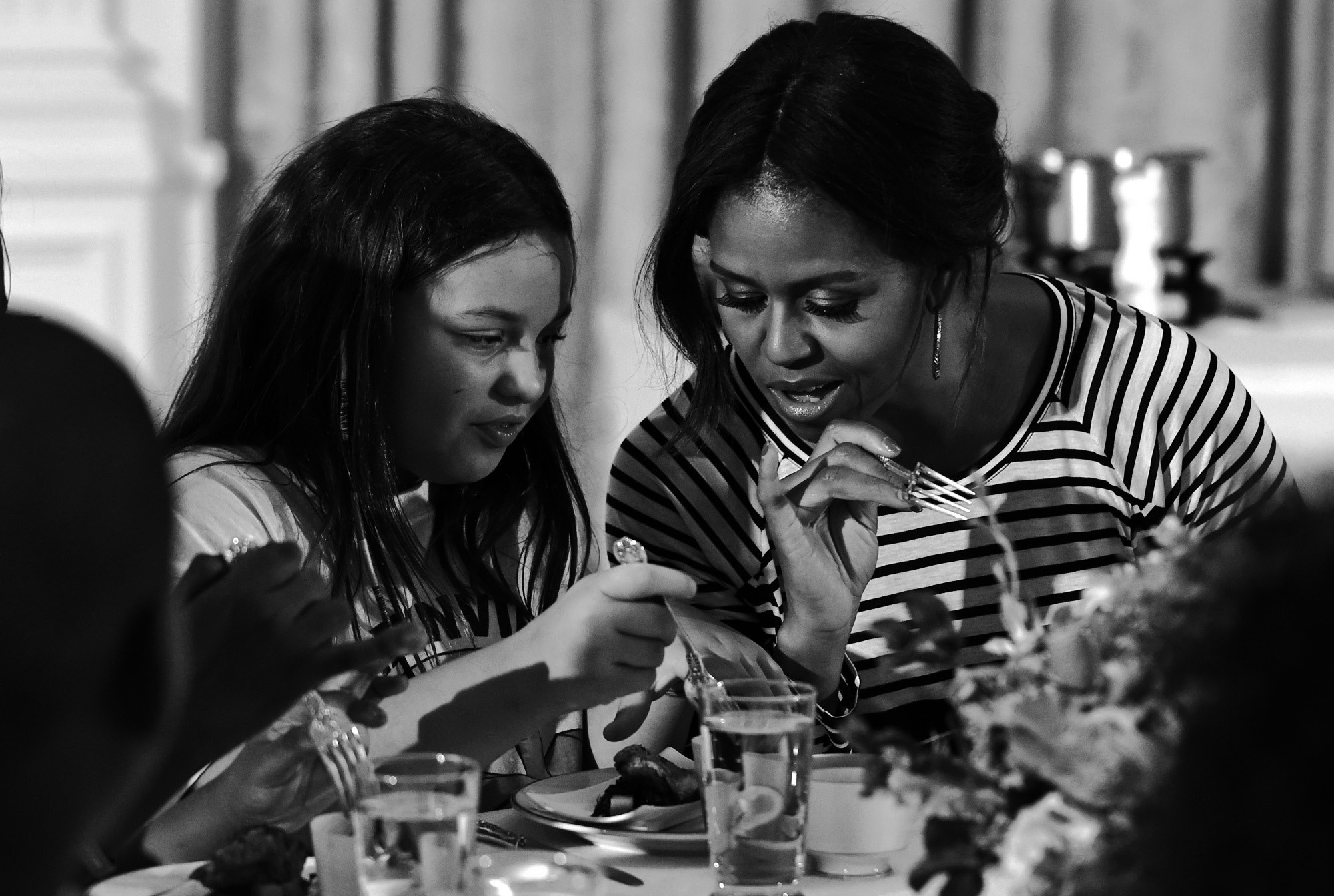 In this 2014 file photo, first lady Michelle Obama and a student look over their plates as they eat lunch in the East Room of the White House in Washington following the annual fall harvest of the White House Kitchen Garden.
