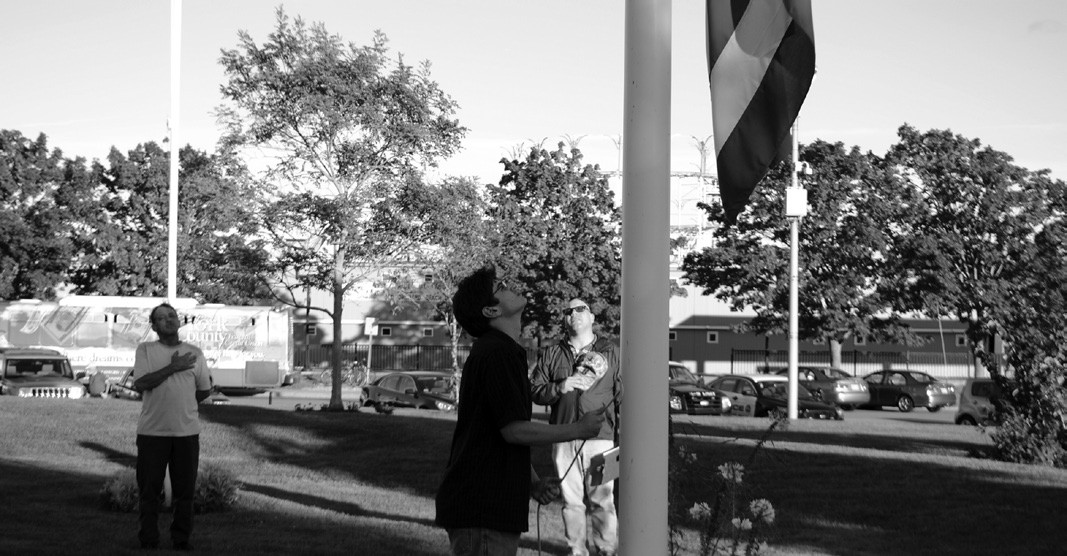Jay Chase and Anthony Massarelli salute as Jesse Raymond raises the American flag at a ceremony at Veterans Memorial Park in Old Orchard Beach Friday evening.