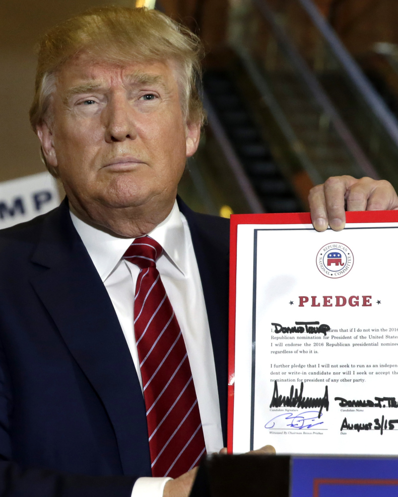Republican presidential candidate Donald Trump holds his pledge during a news conference at Trump Tower on Thursday.