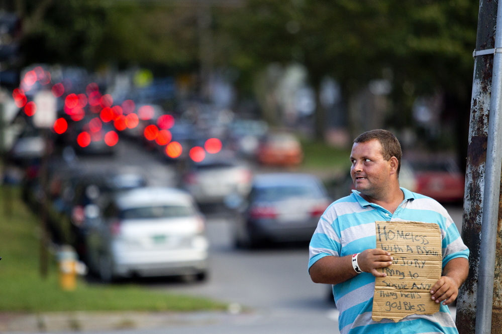 """Louis Walker, 32, of Portland, panhandles for money at the corner of State Street and Park Avenue on Friday evening. Walker, who lives with his wife in a tent in the woods, says he's been panhandling for about three weeks. """"I'm glad they're keeping it legal,"""" he said."""