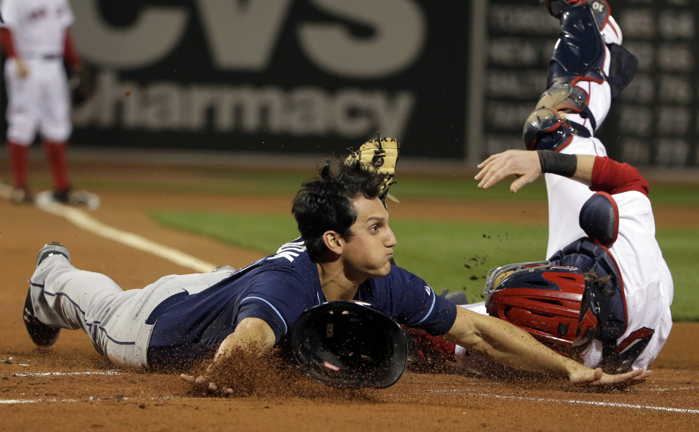 Tampa Bay's Mikie Mahtook slides safely into home as Red Sox catcher Ryan Hanigan tries to tag him out in the first inning.
