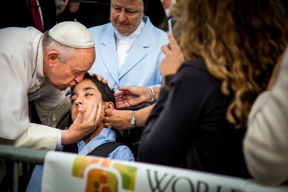 Pope Francis kisses and blesses Michael Keating, 10, of Elverson, Pa., after arriving in Philadelphia Saturday.