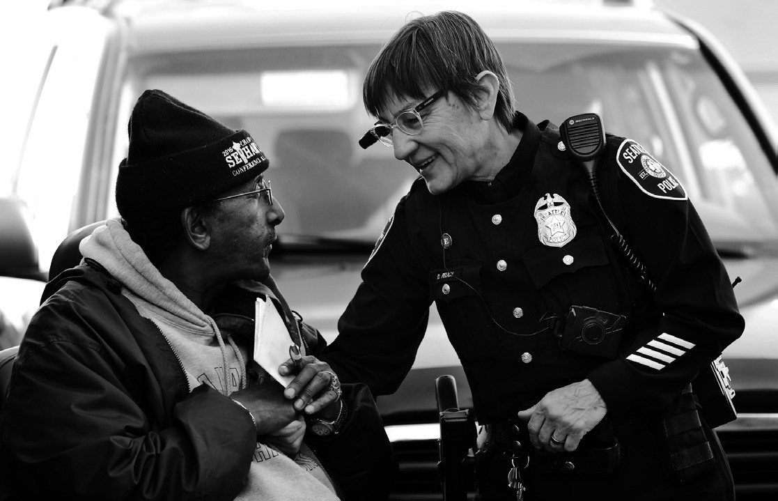 In this March 12 file photo, Seattle police officer Debra Pelich, right, wears a video camera on her eyeglasses as she talks with Alex Legesse before a small community gathering in Seattle.