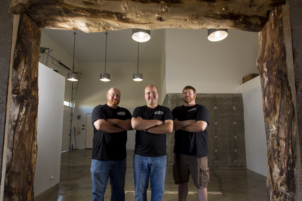Fore River Brewing Co. co-founders Alex Anastasoff, left, John LeGassey and T.J. Hansen, right, stand in their soon-to-be-renovated facility. Once opened, the brewery will join a crowded landscape of beer companies in Maine.