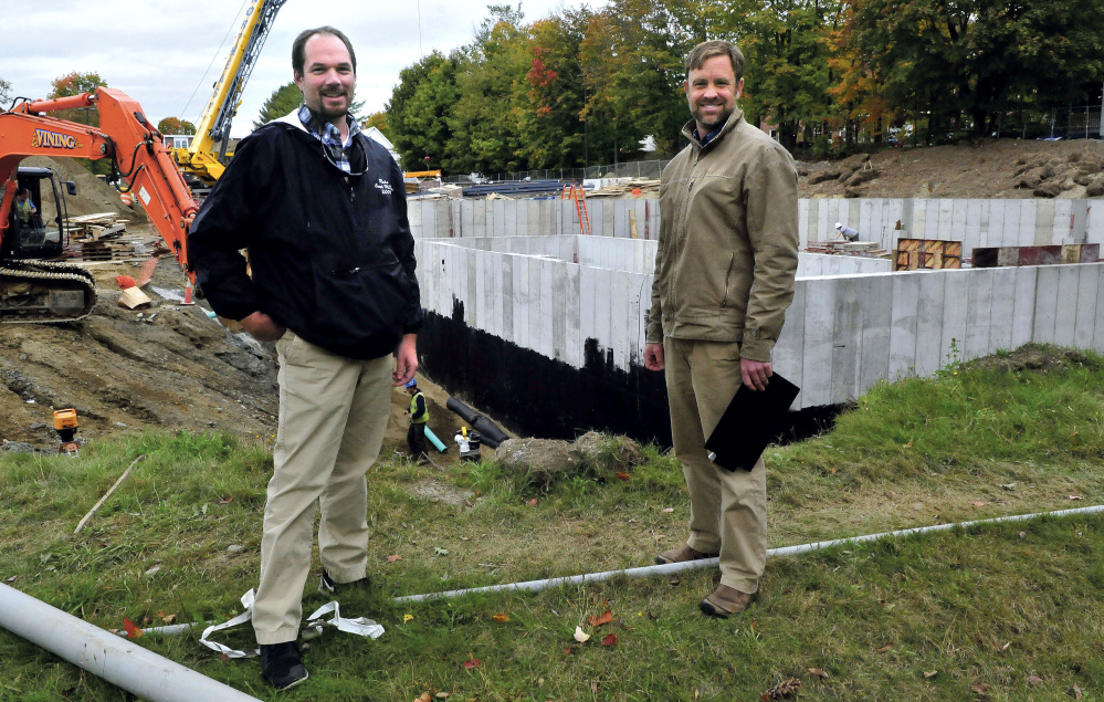 Jeff McKay, left, director of facilities management at the University of Maine at Farmington, and Luke Kellett, coordinator of the Sustainable Campus Coalition, outside the biomass central heating plant construction.