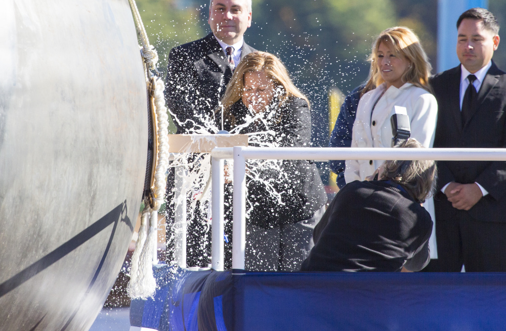 Rosa Peralta is flanked by family as she christens the USS Rafael Peralta on Saturday at Bath Iron Works. The ship is named for Peralta's son, a U.S. Marine Corps sergeant who was killed in action in 2004 in Iraq. The ship is the 35th Arleigh Burke-class destroyer built at BIW.