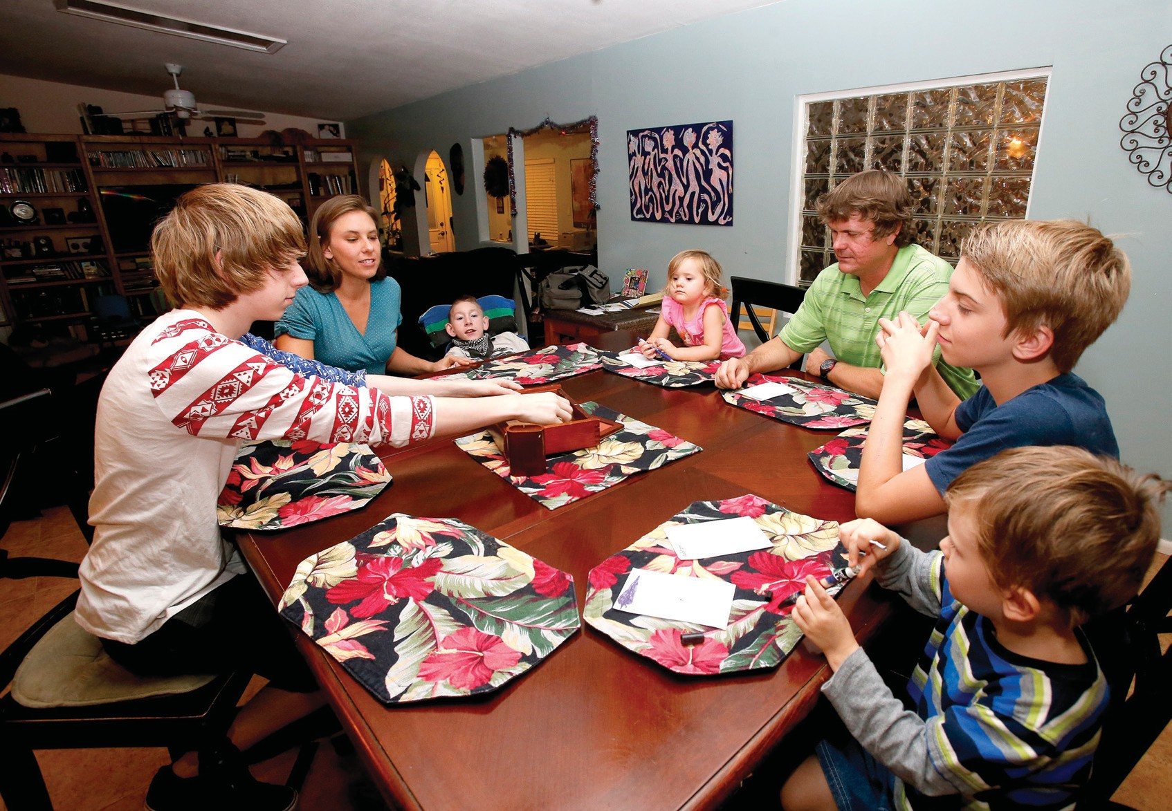 """In this Wednesday photo, pictured from left to right, are, Jo Armstrong, Julie Armstrong, Skylar Armstrong, Amelia Anderson, Nathan Anderson, Westley Armstrong and Dean Anderson sit together for a game at their home in Tucson, Ariz. At 42 with a blended family of five, Nathan Anderson runs an acupuncture clinic with his wife, Julie, also an acupuncturist. Combined, their monthly student loans bills approach $1,700. """"More than we spend on groceries and kind of like having a second mortgage,"""" Nathan said."""