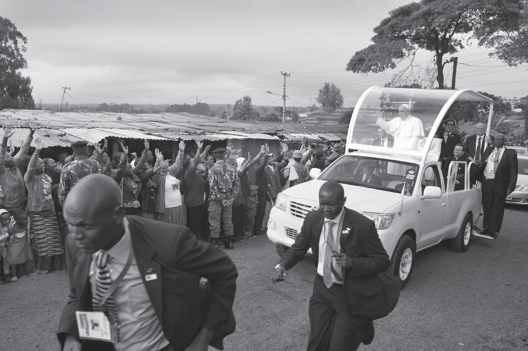 Pope Francis waves to local residents as he drives to St. Joseph The Worker Catholic Church in the Kangemi slum of Nairobi, Kenya Friday.