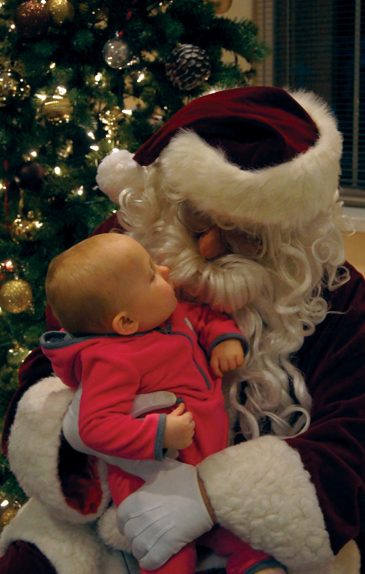 Santa holds a baby Thanksgiving evening at the Saco Fire Station, during his annual visit.