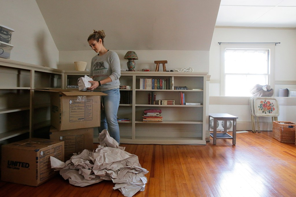 Ivy McGrew unpacks boxes in her new apartment in Portland's West End.