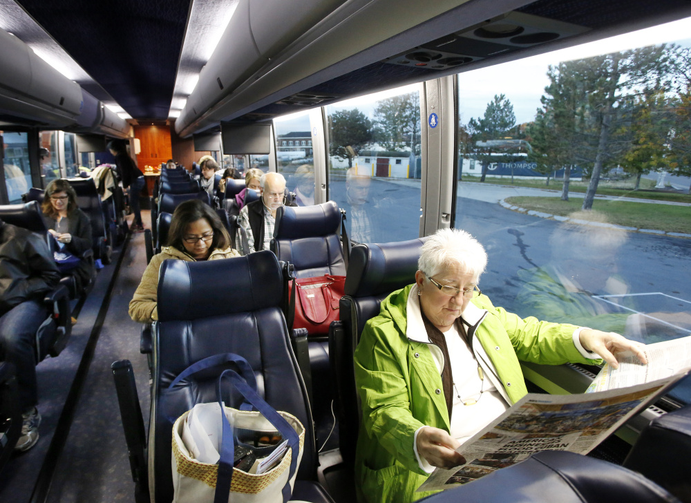 Karen Roen of Waldoboro reads a paper while waiting to depart from the Portland Transportation Center for New York City on Monday morning.