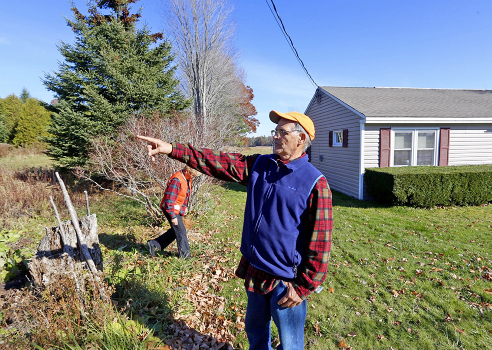 Dick Arsenault points to Turkey Lane in front of his house in Buxton, where a fatal car crash happened early Thursday morning. His wife, Elaine, is in the background. The couple say the body of a girl ended up in their side yard, only a few feet from their house.