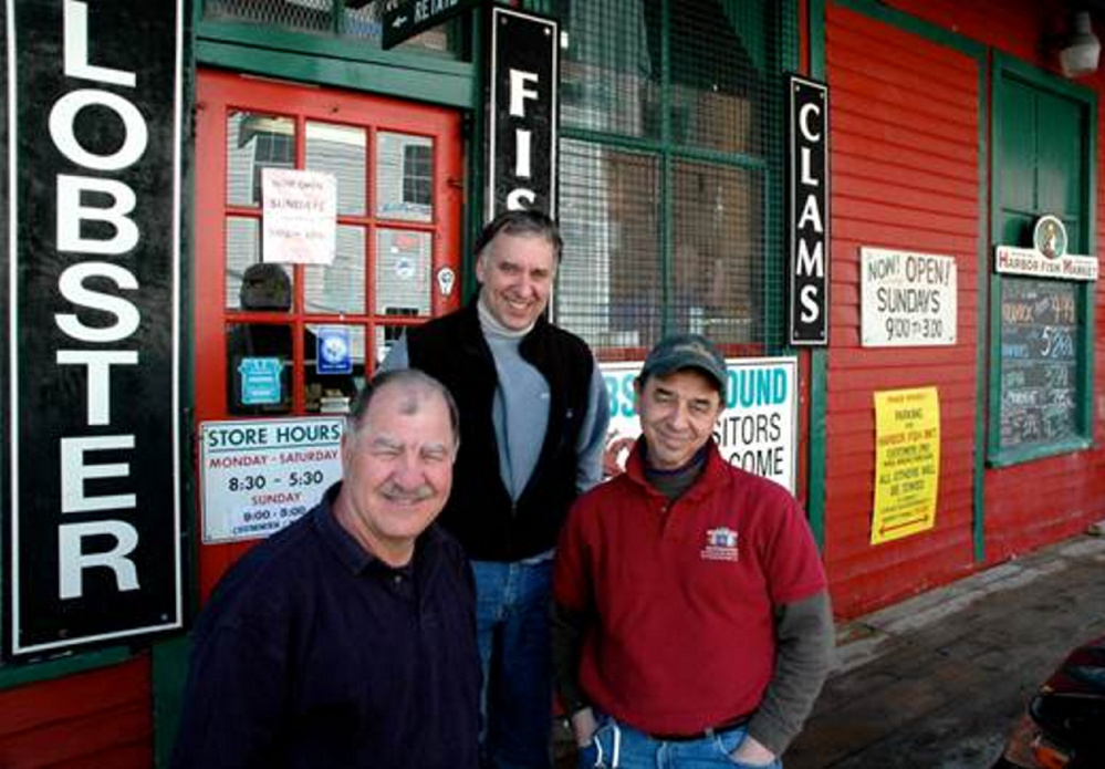 The Alfiero brothers outside Harbor Fish Market, at 9 Custom House Wharf, in Portland,  took over the business from their father in 1990s. From left to right, Nick Alfiero, 65, of Scarborough, Mike Alfiero, 56, of Cape Elizabeth, and Benjamin Alfiero, 59, of Scarborough.