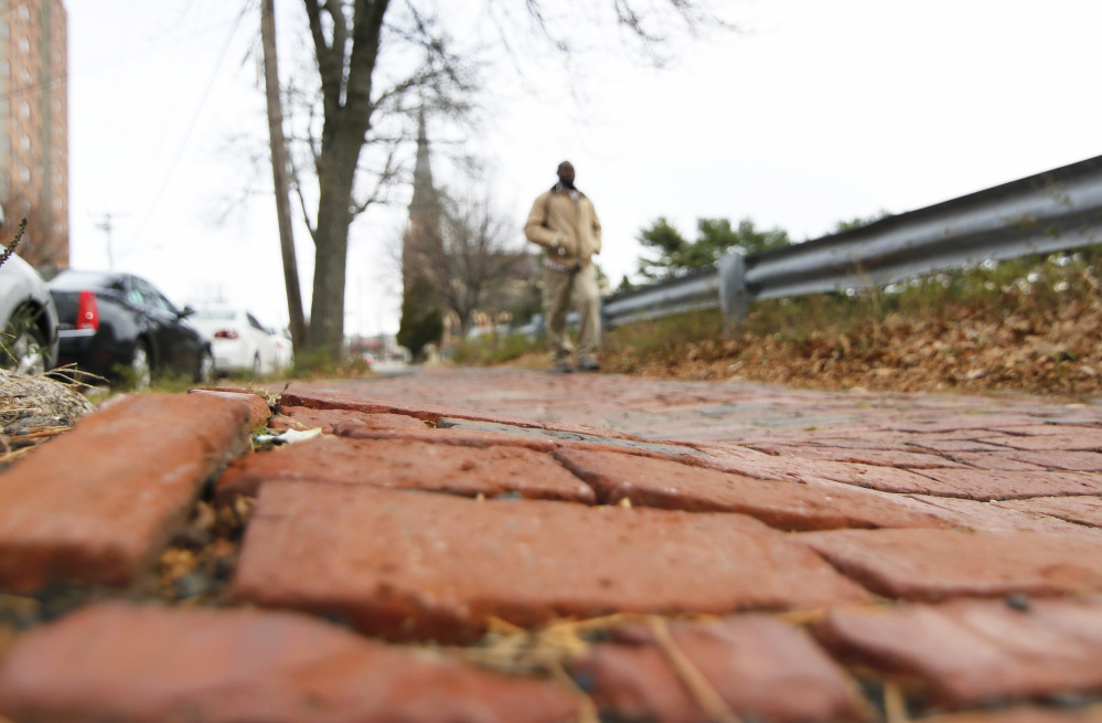 A pedestrian makes his way along the uneven brickwork between Pearl and Franklin streets in Portland.