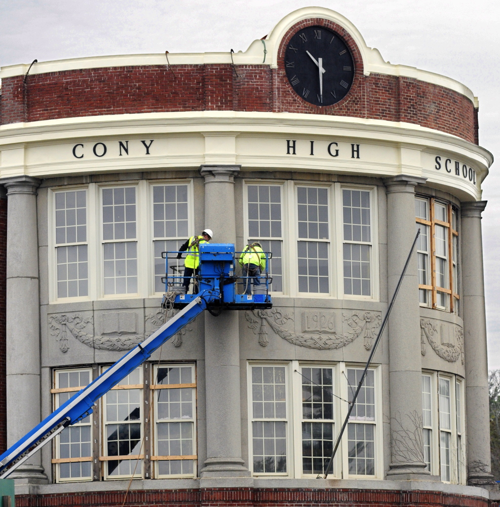Construction workers high on a lift above Cony Circle in October 2014 work on windows of the curved facade of the former Cony High School flatiron building in Augusta. The 1926 building was converted into senior citizens' housing, a project honored by Maine Preservation last week.