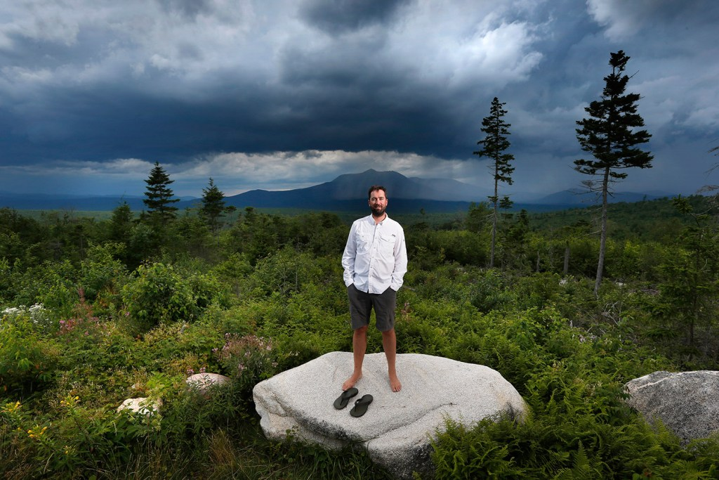 Lucas St. Clair, who is managing a nonprofit foundation set up to promote the creation of a park on about 70,000 acres owned by his mother, Burt's Bees founder Roxanne Quimby, stands on the land proposed for the park in Penobscot County, Maine. Mount Katahdin, the state's highest peak, can be seen in the background as a rainstorm passes through Baxter State Park.