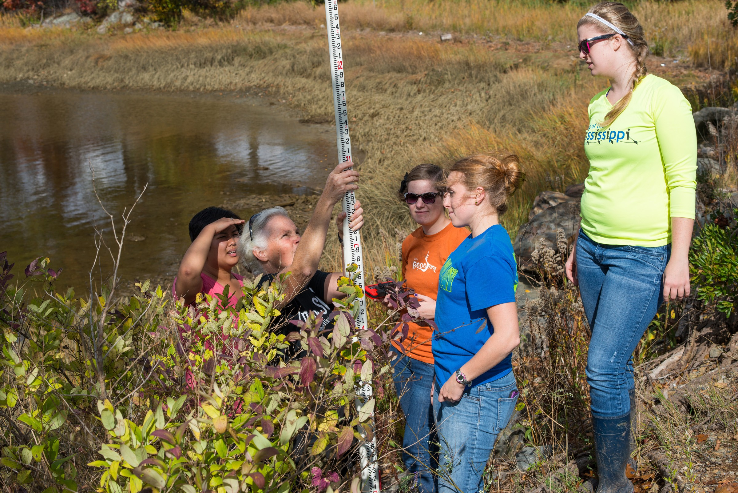 University of New England Environmental Studies students work with UNE Associate Professor Pam Morgan to survey elevations along the Saco River in order to map sea levels.