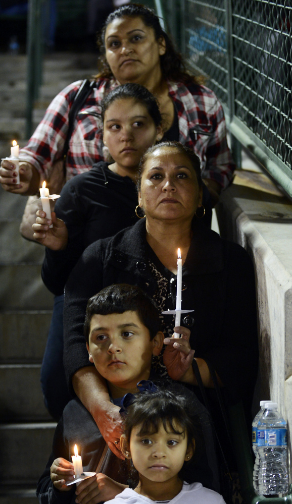 Elda Flores, center, and her family attend a vigil in San Bernardino, Calif., for victims of the shootings there. Gun violence claims over 30,000 lives a year in the U.S.