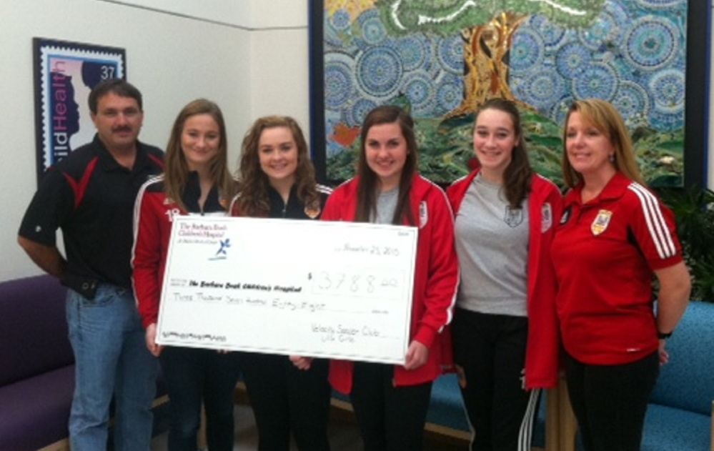 Velocity Soccer Club coach Rick Doyon and team members, from left, Natalia Profenno of Saco, Sarah Champagne of Buxton, Erin Gorton of Kennebunk and Camryn Morton of Gorham, and coach Laurie Holbrook present the team's donation of $3,788 to the Barbara Bush Children's Hospital at Maine Medical Center in Portland.
