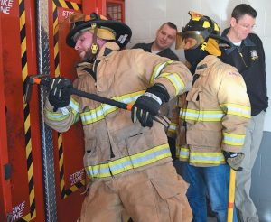 RUSSIAN FIREFIGHTERS Victor Kozelskii and Sergi Kvashnin work together to get through a door breaching mock-up during Thursday's visit in Brunswick.