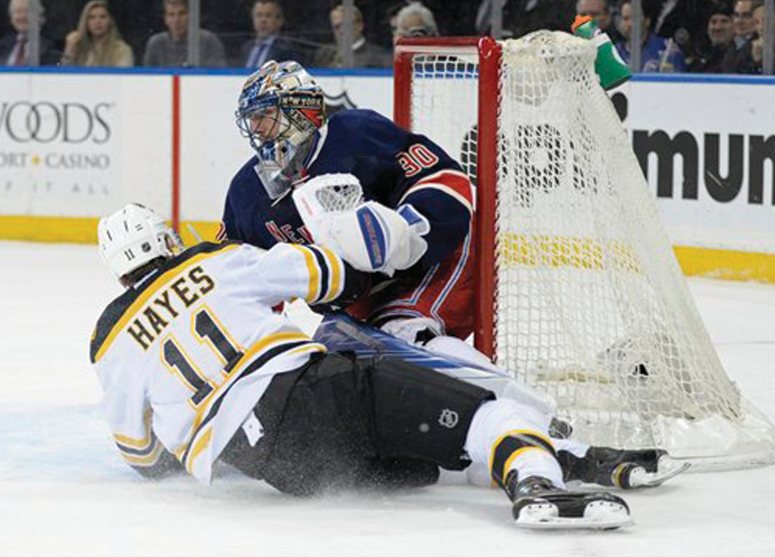Boston Bruins' Jimmy Hayes (11) slides into New York Rangers goaltender Henrik Lundqvist (30), of Sweden, during the first period Monday, at Madison Square Garden in New York.