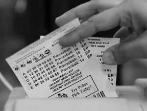 MOMTAZ PARVIN PULLS POWERBALL LOTTERY TICKETS from the printer at her store in Oklahoma City Jan. 8. As there was no winner for the jackpot on Jan. 9, lottery officials say the prize has swelled to an estimated $1.3 billion — the world's largest prize ever.
