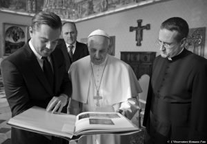 POPE FRANCIS browses through the book of paintings by Hieronymus Bosch he was presented by actor Leonardo DiCaprio, left, during a private audience in the pontiff's studio, at the Vatican on Thursday.