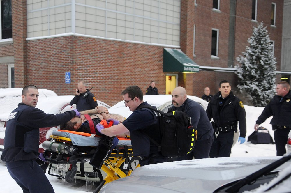 Firefighters and police escort Jason Begin, who was shot by Augusta Police Officer Laura Drouin on Jan. 12, 2015, following a confrontation at an office at the former MaineGeneral Medical Center in Augusta. Staff file photo by Andy Molloy