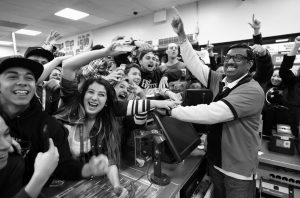 7-ELEVEN STORE CLERK M. FAROQUI celebrates with customers after learning the store sold a winning Powerball ticket on Wednesday in Chino Hills, California. One winning ticket was sold at the store located in suburban Los Angeles said Alex Traverso, a spokesman for California lottery. The identity of the winner is not yet known.