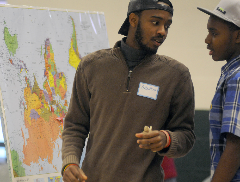 Arnaud Nahimana, left, and his brother, Nelson, place pins on a map of their native country, Burundi, during a Martin Luther King Day forum in Winthrop. The teens live in Biddeford.